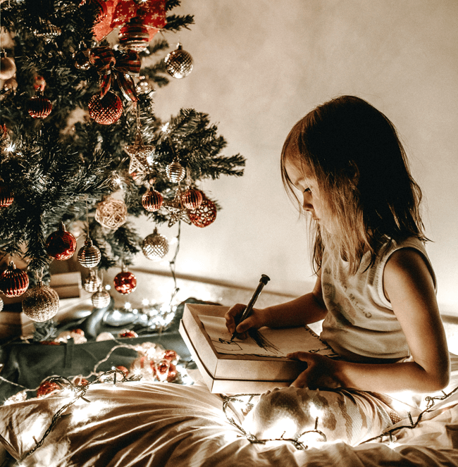 Girl opening christmas present under tree