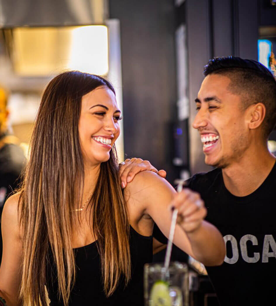 Bartender and server laughing