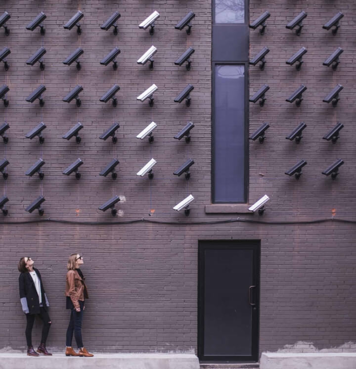 Two people looking up at a wall of security cameras
