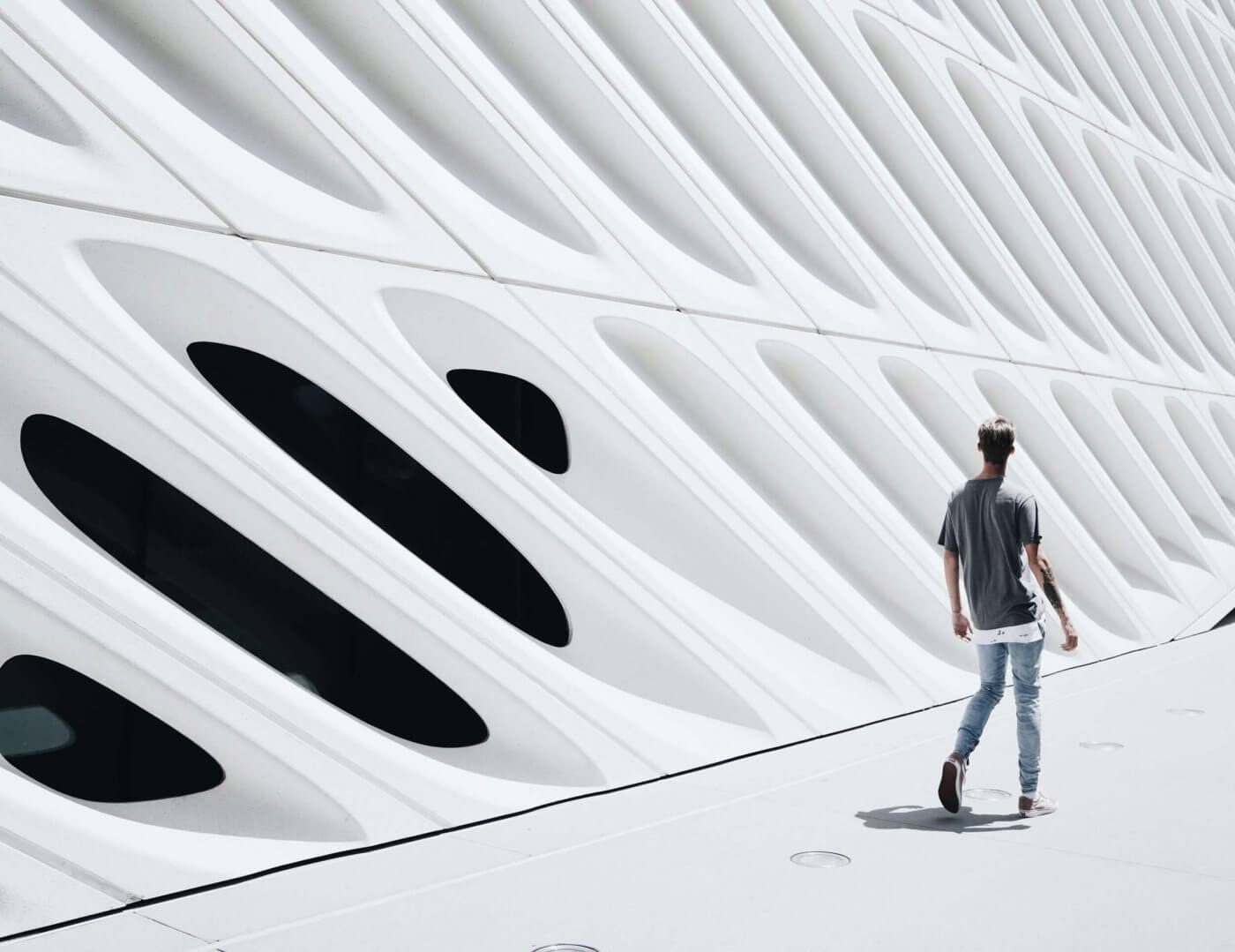 Man walking infront of modern building
