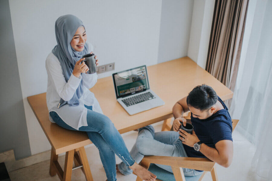 young people laughing near laptop